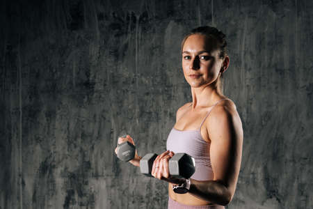 Middle shot portrait of muscular young athletic woman with perfect body in sportswear holding dumbbell during weight training workout. Caucasian fitness female posing in studio with dark background.