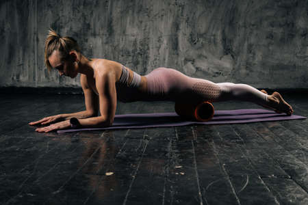 Muscular young athletic woman with perfect beautiful body in sportswear massaging legs and hips, using fitness roller and doing plank lying on yoga mat. Caucasian fitness female posing in studio.