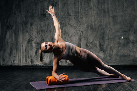 Muscular young athletic woman with perfect beautiful body in sportswear doing side plank pose using foam roller massager on mat. Caucasian fitness female practicing yoga doing Vasisthasana exercise