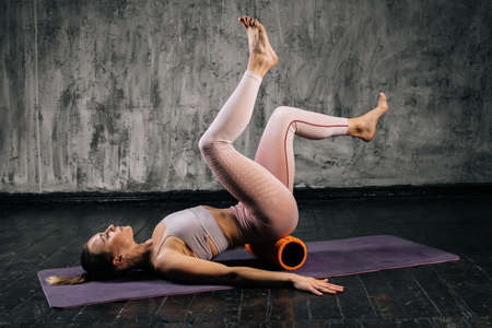 Muscular young athletic woman with perfect beautiful body in sportswear doing exercises using fitness roller lying on yoga mat. Caucasian fitness female posing in studio with dark grey background.