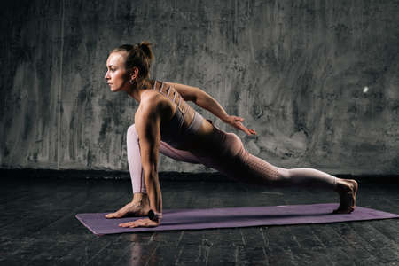 Front view of muscular young athletic woman with perfect beautiful body wearing sportswear practising posture on yoga mat. Caucasian fitness female posing in studio with dark grey background.