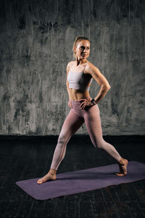Vertical portrait of muscular young athletic woman with perfect beautiful body wearing sportswear holding hands on waist and lunging forward. Caucasian fitness female posing in studio