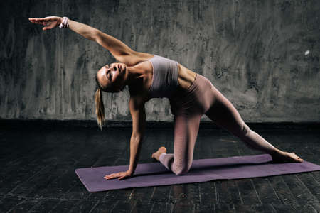 Muscular young athletic woman with perfect beautiful body wearing sportswear warm up training stand tilt body to sides with hands on yoga mat. Caucasian fitness female posing in studio.