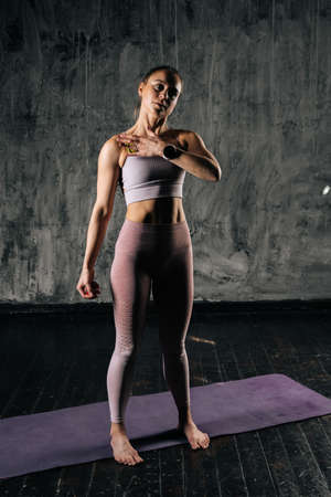 Vertical portrait of young athletic woman with perfect beautiful body wearing sportswear using small massaging ball on leg. Caucasian fitness female posing in studio with dark grey background.