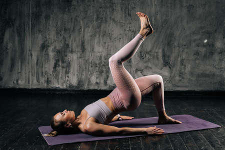 Muscular young athletic woman with perfect beautiful body wearing sportswear doing workout for legs lying on yoga mat. Caucasian fitness female posing in studio with dark grey background.