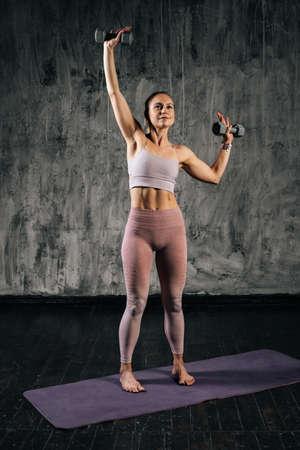 Vertical portrait of muscular young athletic woman with perfect beautiful body wearing sportswear lifting two dumbbells over head. Caucasian fitness female posing in studio with dark grey background.