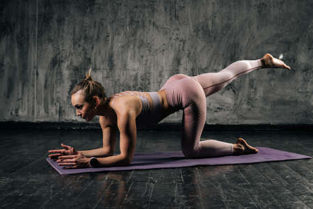 Front view of muscular young athletic woman with perfect beautiful body wearing sportswear exercising buttocks legs on yoga mat. Caucasian fitness female posing in studio with dark grey background.