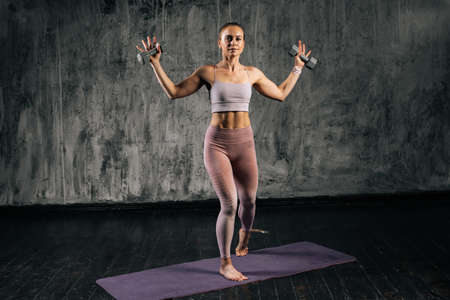 Portrait of muscular young athletic woman with perfect beautiful body wearing sportswear raising arms holding dumbell. Caucasian fitness female posing in studio with dark grey background.