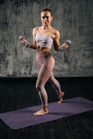 Vertical portrait of muscular young athletic woman with perfect beautiful body wearing sportswear doing exercise with lifting weights and lunging forward. Caucasian fitness female posing in studio.