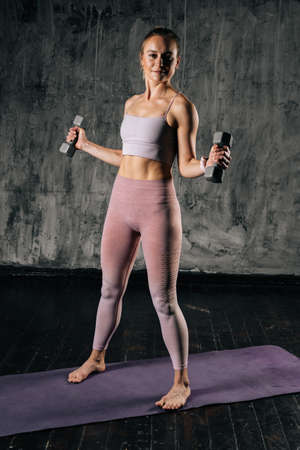 Vertical portrait of young athletic woman with perfect beautiful body wearing sportswear exercising with dumbbells. Caucasian fitness female posing in studio with dark grey background.