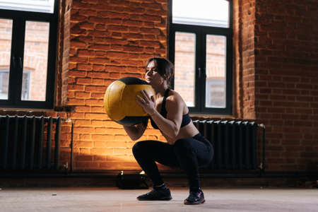 Medium shot of young athletic woman with strong body wearing sportswear doing squats with heavy medicine ball during workout training. Caucasian fitness female workout out exercising in dark gym.