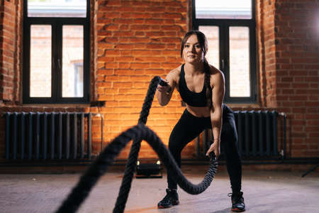Low-angle view of fitness young athletic woman with strong beautiful body in black sportswear exercising with battle ropes having workout training. Muscular Caucasian female workout out in dark gym. Stock fotó
