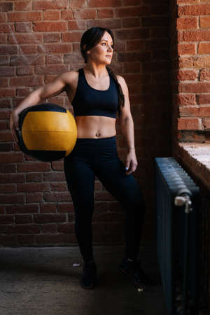 Vertical portrait of fitness young athletic woman with strong beautiful body in black sportswear posing with heavy medicine ball by window. Muscular Caucasian female workout out in dark gym.