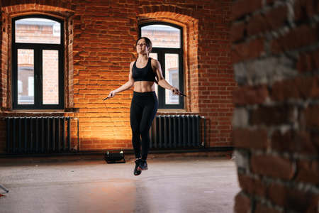 Wide shot of fitness young athletic woman with strong beautiful body in sportswear exercising with jumping rope during workout training. Muscular Caucasian female workout out in dark gym.