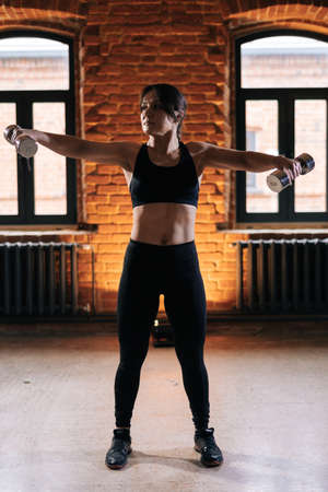 Vertical portrait of young athletic woman with beautiful strong body wearing activewear holding dumbbells on retracted arms. Caucasian fitness female workout out exercising in dark gym.