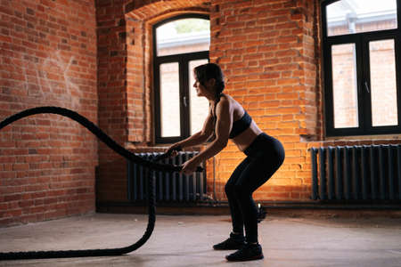Side view of fitness young athletic woman with strong beautiful body in black activewear exercising with battle ropes having workout training. Muscular Caucasian female workout out in dark gym. Stock fotó