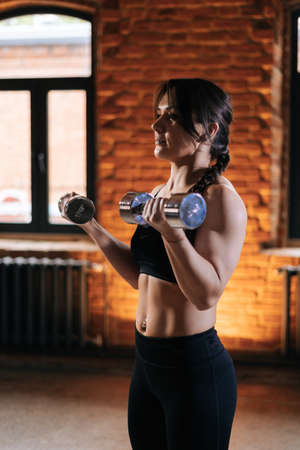 Medium shot portrait of young athletic woman with beautiful strong body in sportswear exercising with dumbbells during workout training. Caucasian fitness female workout out exercising in dark gym.