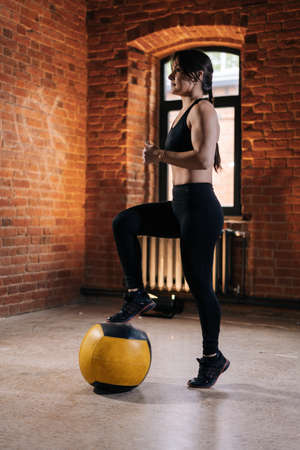 Muscular young athletic woman with strong beautiful body in sportswear exercising with heavy medicine ball during workout training. Caucasian fitness female workout out exercising in dark gym. Stock fotó