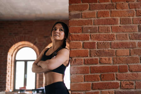Portrait of muscular young athletic woman with strong beautiful body in black sportswear standing with arms crossed by brick wall. Caucasian fitness female workout out exercising in dark gym