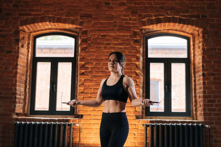 Medium shot portrait of fitness young athletic woman with strong beautiful body in sportswear exercising with jumping rope during workout training. Muscular Caucasian female workout out in dark gym.
