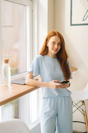 Medium shot vertical portrait of smiling attractive young woman using phone , typing online messages standing by window in cafe. Pretty redhead Caucasian lady having leisure activity in coffee shop.