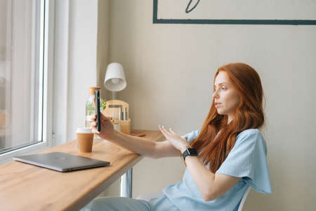 Medium shot of attractive young woman video call on smartphone drinking coffee sitting at table with laptop by window in cafe. Pretty redhead Caucasian lady having leisure activity in coffee shop.