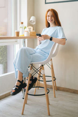Vertical portrait of happy young woman in casual clothing holding mobile phone sitting at desk by window in cozy light cafe. Pretty redhead Caucasian lady having leisure activity in coffee shop.