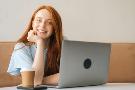 Close-up portrait of cheerful young beautiful woman sitting at desk with laptop and cup with hot coffee at cozy cafe, looking at camera. Pretty redhead Caucasian lady remote working or studying.