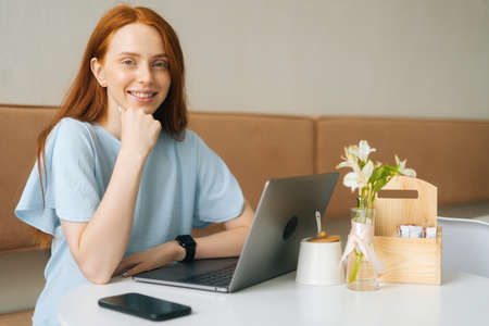 Portrait of smiling attractive young woman sitting at table with laptop and phone in cafe with warm daylight and looking at camera. Pretty redhead Caucasian lady remote working or studying.