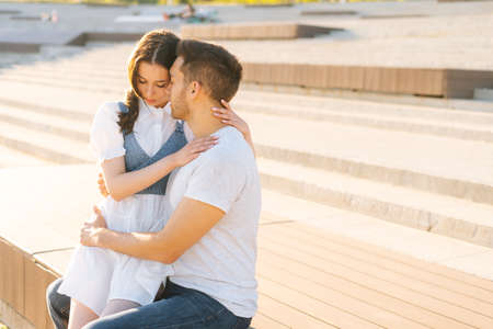 Portrait of happy young couple resting in city park sitting higging on bench in summer sunny day. Relationships between cheerful boyfriend and girlfriend enjoying spending time together outdoors. Stock fotó