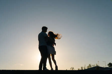 Silhouette of loving young couple hugging at sunset on background of cloudless sky in evening, full length. Happy Caucasian couple in love having romantic walk outdoors enjoying time together.