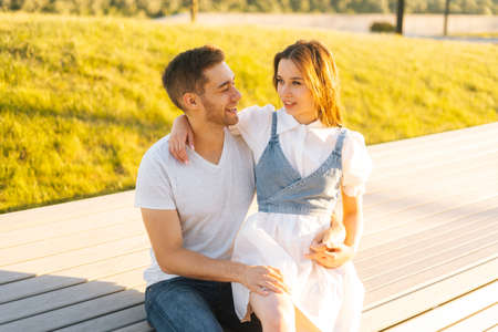 Portrait of cheerful young couple relaxing sitting on bench in summer sunny day on blurred background of green grass. Happy couple in love having romantic walk outdoors enjoying time together. Stock fotó