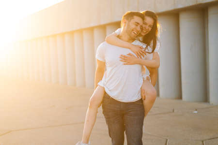 Portrait of cheerful young couple having fun embracing and enjoying summer time together at sunset on background of bright sunlight. Happy Caucasian couple in love having romantic walk outdoors. Stock fotó