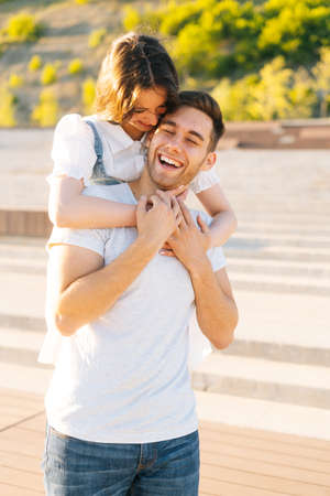 Vertical portrait of happy young couple having fun in city park in summer sunny day, young woman hanging on shoulders of laughing lover. Relationships boyfriend and girlfriend enjoying outdoors. Stock fotó