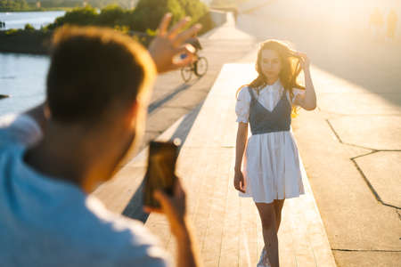 Close-up back view of young man taking picture of girlfriend on phone at sunset in city park during romantic walk. Cute Caucasian woman posing for male photographer on background of bright sunbeam.