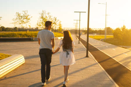 Rear view of young couple in love holding hands walking in city park in sunny summer day on background of bright sunlight. Happy relationships between boyfriend and girlfriend enjoying time together.