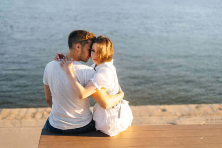 Portrait of beautiful young happy couple in love hugging, sitting on bench on city waterfront near river in sunny summer day. Handsome man sitting back forward, woman is looking at camera.
