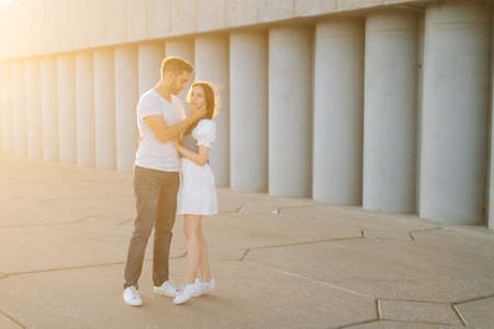 Full length shot portrait of romantic young couple in love embracing while man touching neck of girlfriends with hand, in city park at sunset on background of warm bright sunlight. Stock fotó