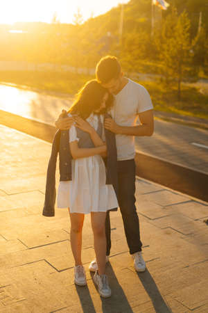 Vertical portrait of charming young couple in love hugging in summer evening on background of warm sunlight. Happy relationships between boyfriend and girlfriend enjoying time together.