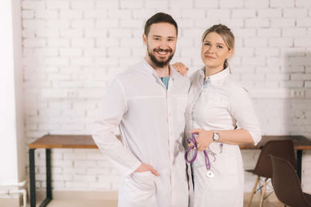 Portrait of two cheerful successful professional doctors wearing white lab coat uniform posing together standing on background of white brick wall, looking at camera.