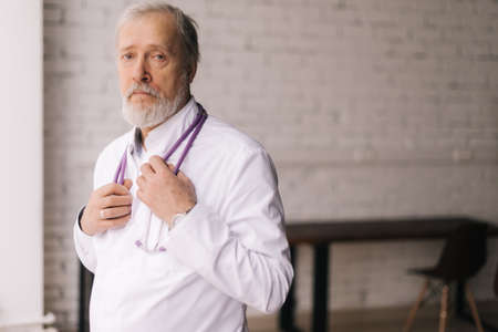 Medium shot portrait of confident mature male doctor in white lab coat and stethoscope standing in light hospital office room. Professional adult physician with white beard and grey hair at workplace.