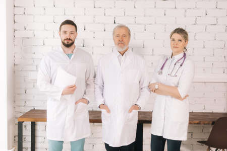 Portrait of three experienced successful professional doctors wearing hospital uniform posing standing on background of white brick wall and looking at camera.