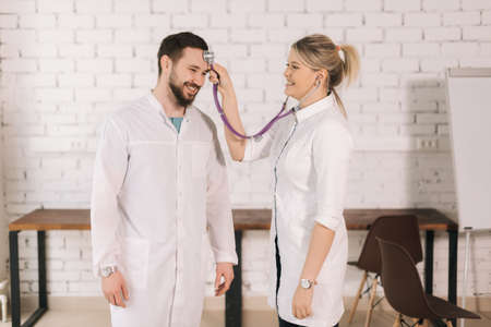 Portrait of two cheerful doctors having fun, young woman nurse checking with stethoscop forehead of male physician, on background of white brick wall. Stock fotó