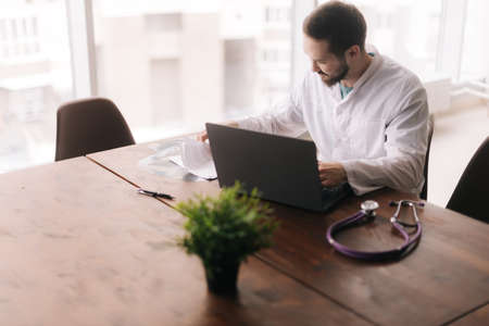 High-angle view of young male doctor wearing white coat working with patient health data sitting at desk with laptop in the hospital office, on background of window, selective focus. Stock fotó
