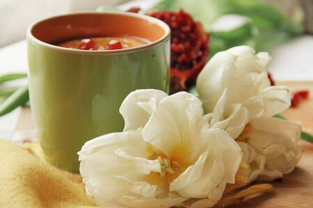 Tender white flower and cup of tea with pomegranate