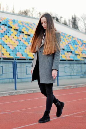 Sensual portrait of beautiful young girl walking in the old abandoned stadium on cold autumn day. Caucasian female model in front of sits. Human emotions, facial expression, fashion, sport, lifestyle.