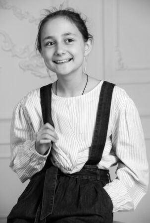 Smile. Portrait of little brunette caucasian girl in casual clothes. Cute female model smiling and posing, looking at side. Childhood, style, art photo, beauty and fashion concept. Black n white shot.