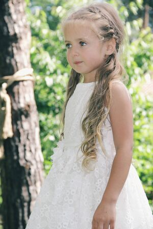 Portrait of little caucasian girl wearing white princess dress for celebration event. Cute female model looks dreamful, tender. Childhood, art, style, pure beauty, fashion concept. Human emotions.