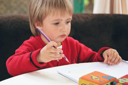 First steps in life. Portrait of little caucasian boy in casual clothes studying at home. Cute male model trying to draw, write, read. Childhood, art, style, beauty, education and fashion concept. Stock Photo