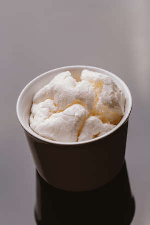 Fresh meringue in light bowl on a dark background. Stock Photo